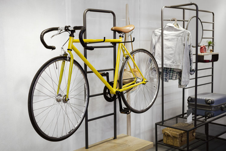 Yellow Bicycle Hanging On Rack Against Wall At Home