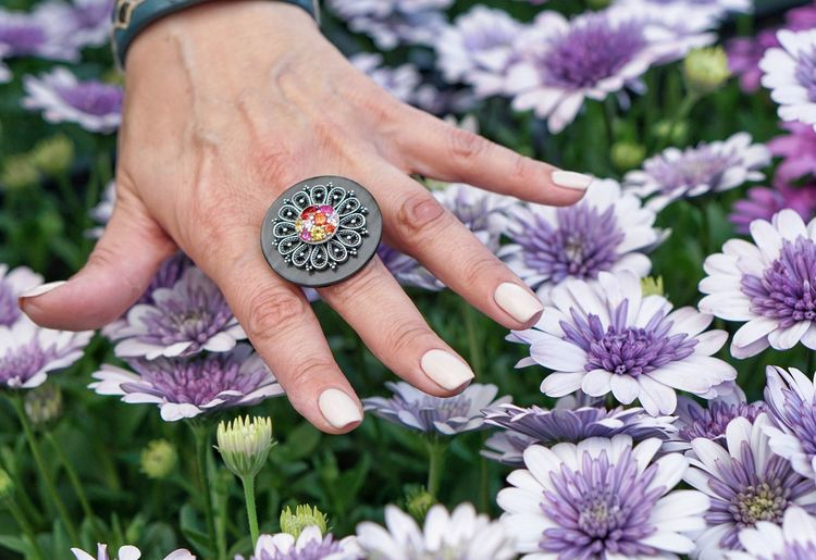 Cropped Hand Showing Ring Over Purple Flowers In Field
