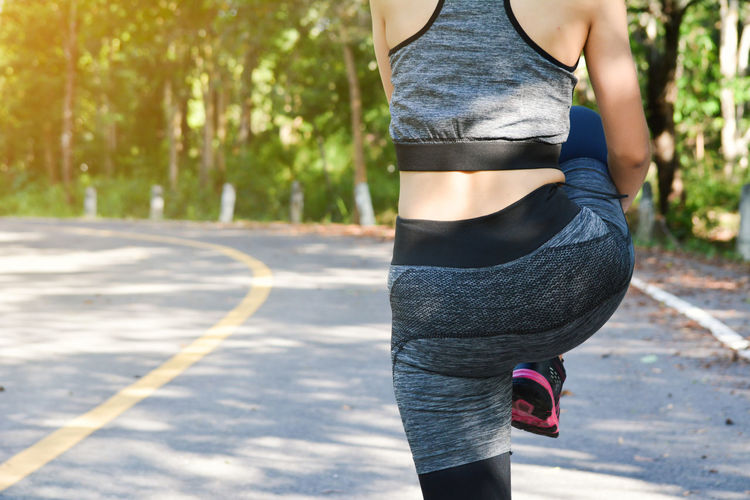 Midsection of woman with sports clothing warming up while standing outdoors