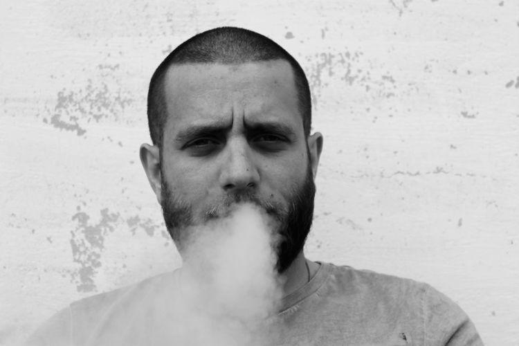Portrait of man exhaling smoke