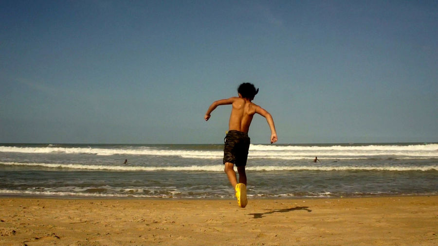 Shirtless boy running towards sea at beach against clear sky