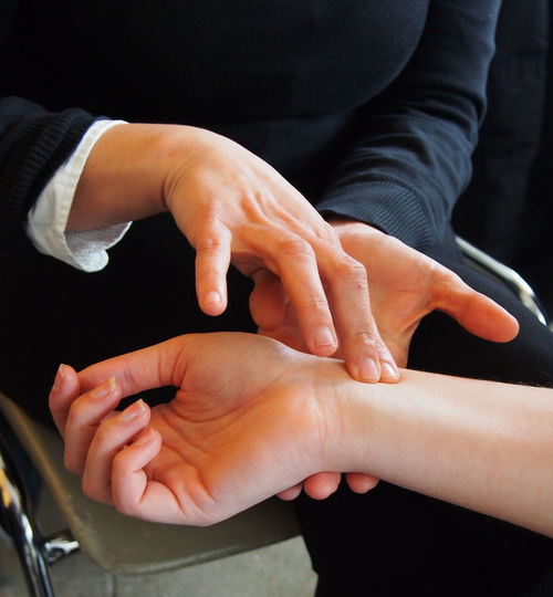 Midsection Of Doctor Checking Pulse Of Patient