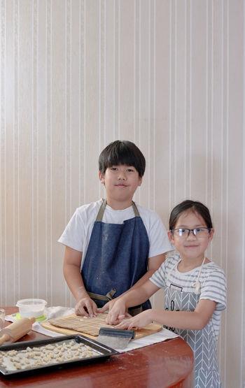 Portrait of siblings preparing cookies on table at home