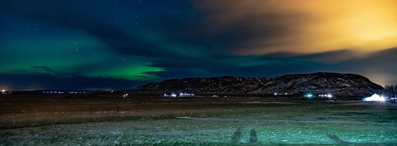 Scenic view of illuminated landscape against dramatic sky at night