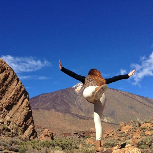 Woman with arms outstretched standing on one leg against mountains