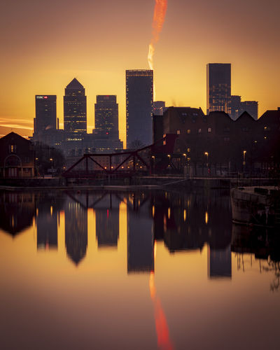 Reflection of buildings in city during sunset