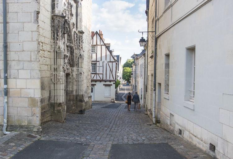 Rear view of people walking on footpath amidst buildings in city