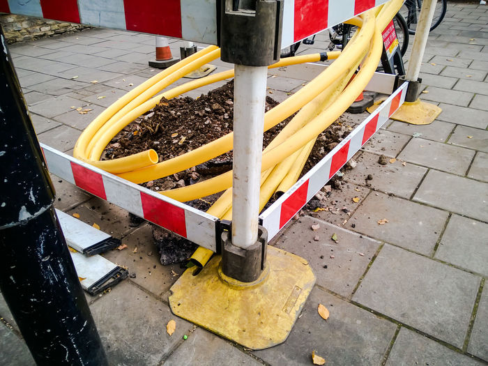 No People Low Section Street Outdoors Paving Stone Day Yellow Barrier Striped Pattern Stripes Pattern Pipes Works Street Works