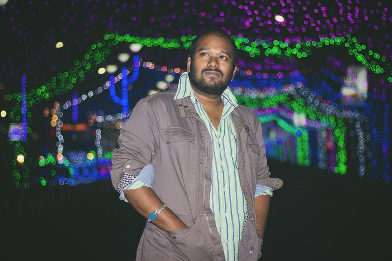 Thoughtful man with hands in pockets standing against illuminated lights