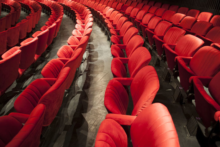 red seats at empty theater Theater Theatre Red Seats Empty Cinema Interior Inside Culture Arts Opéra Traditional Indoors  Entertainment Event Hall Public Amusement  Leisure Nobody Rows Decoration Pattern Chair Velvet Row Seat Classical Comfortable Furniture Show Fancy Formal Audience Film Auditorium MOVIE Performance Showtime Conference Many Detail Modern Above View Floor Wooden Shadow