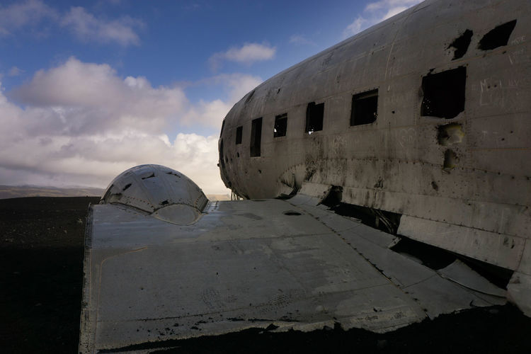 Abandoned airplane on beach against sky