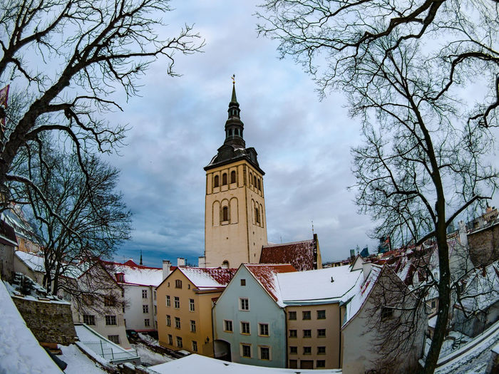 Architecture Bare Tree Building Exterior Built Structure City Clock Cold Temperature Day Nature Niguliste Kirik Outdoors Sky Snow Tallinn Tallinn Old Town Time Tower Travel Destinations Tree Winter