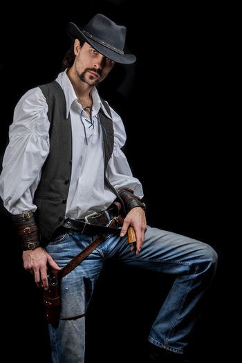 Handsome young man. This is an American cowboy. A vow to a white shirt, brown waistcoat and blue jeans. Black shoes on the feet. Carries a shtyapa, on a belt two pistols. The hair is of medium length; on the face is a beard and mustache. Authentic photo. Culture of America. Cowboy Wild West America American Gun National Authentic Moments Lifestyles Lifestyle One Person Candid Authentic Three Quarter Length Hat Front View Clothing Young Adult Young Men Black Background Men Jeans Males  Standing Real People Handsome