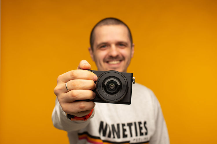 Photographer man holding mirorrless camera in his hand standing at orange background Portrait One Person Looking At Camera Photography Themes Holding Front View Smiling Technology Men Headshot Photographing Camera Camera - Photographic Equipment Happiness Mid Adult Real People Standing Lifestyles Photographic Equipment Digital Camera Photographer\