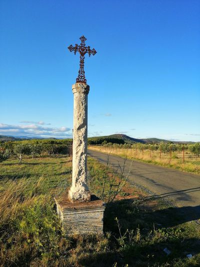 Cross on field against clear blue sky