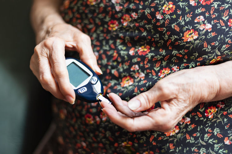 Old lady tracking her glucose levels. Health concept Diabetic Hospital Old Lady Sample Sugar Adult Analyzing Chronic  Diabetes Finger Glucose Hand High Angle View Holding Human Body Part Hypoglycemia Indoors  Insuline Lancet Levels Measurement Meter Real People Testing Tracking