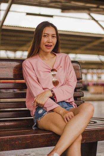 Portrait of woman sitting on bench at railroad station platform