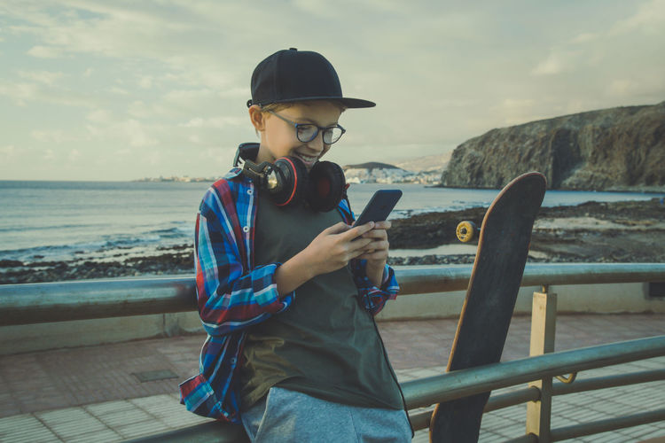 Boy using mobile phone while leaning on railing against beach during sunset