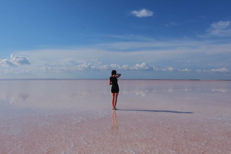 Rear view of woman standing on salt flat against blue sky
