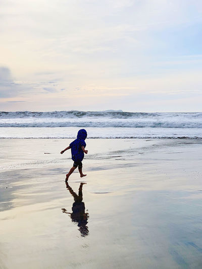 Rear view of boy running at beach