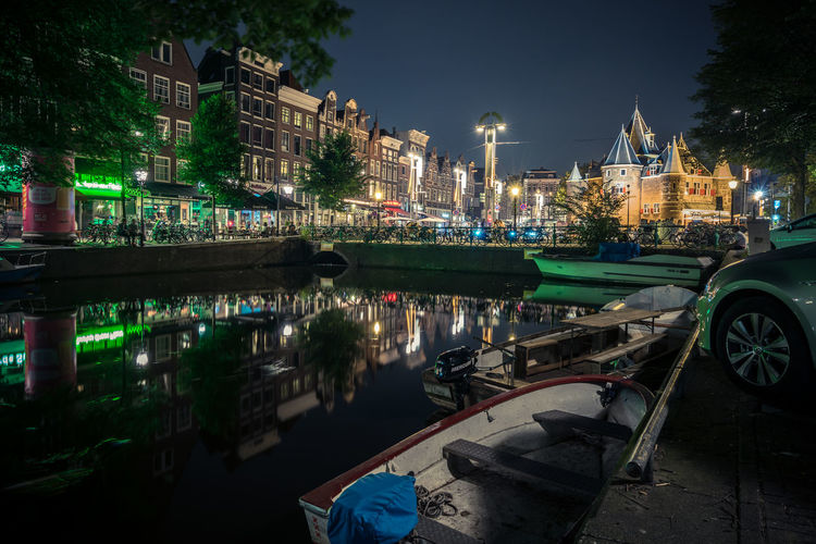 Boats moored on canal against illuminated historic building in city at night