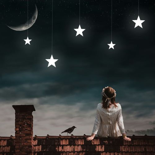 Woman Looking At Artificial Stars Hanging Against Sky