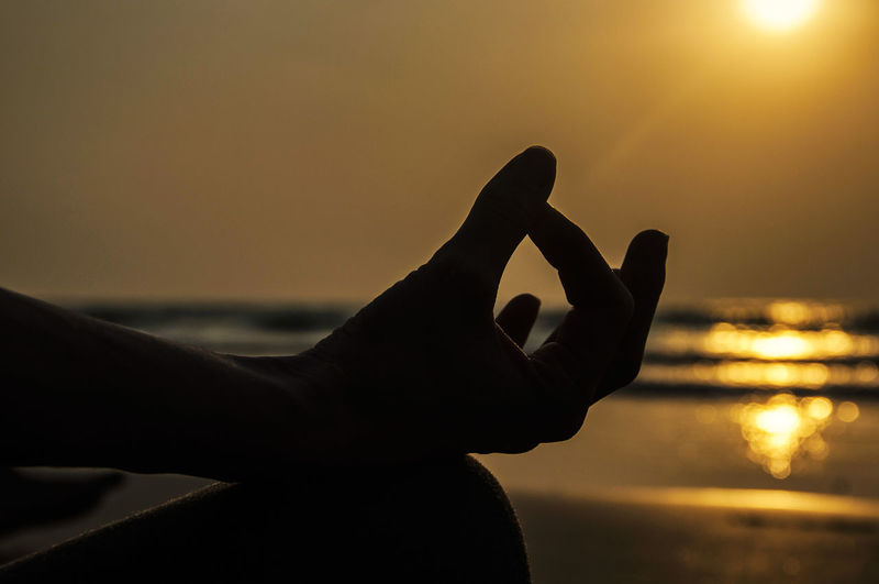 Cropped image of woman practicing lotus position at beach during sunset