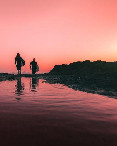 Silhouette people standing by sea against orange sky