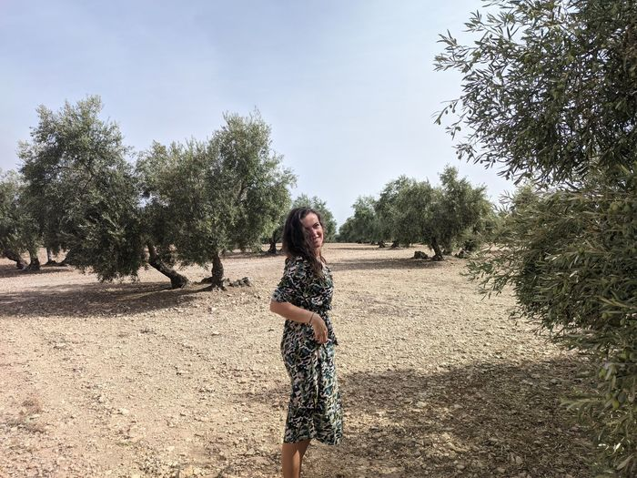 Full length of woman standing by tree against sky