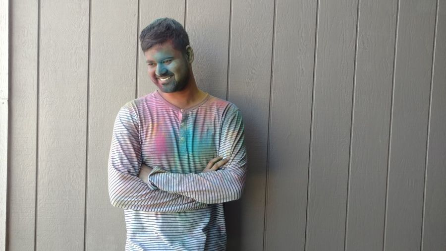 Smiling young man with colorful powder paint looking away while standing against wall