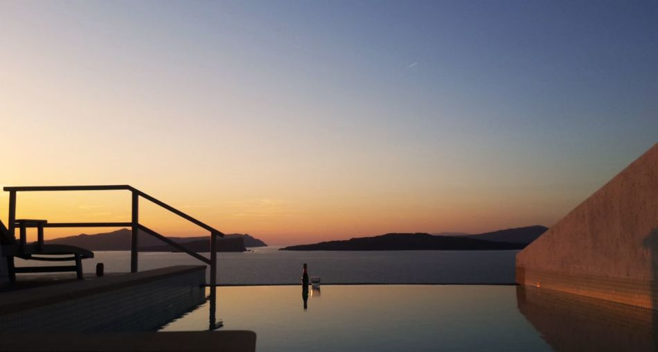 Infinity pool against sky during sunset