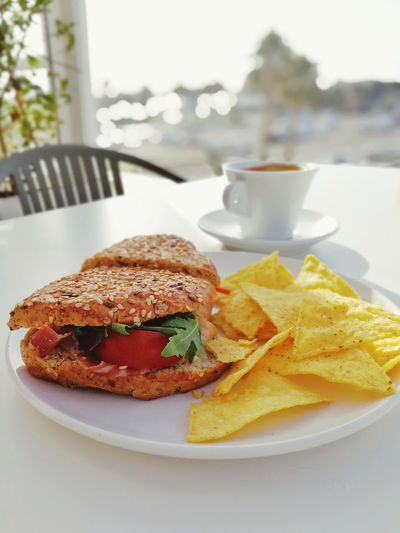 Close-up of fresh sandwich and tortilla chips served in plate with coffee on table