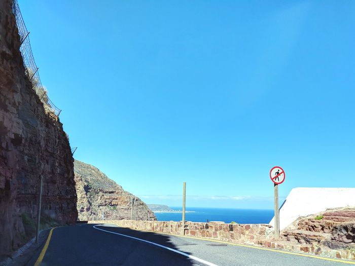 Chapman's Peak Drive, Cape Town Shore Coast Cape Town South Africa Cape Peninsula Summer Sunny Don't Walk No People No Pedestrians Chapmans Peak Drive Chapman's Peak Blue Clear Sky Blue Sky Cloudless EyeEm Selects Road Sign Road Blue Warning Sign Clear Sky Sky Landscape Winding Road Road Warning Sign Mountain Road