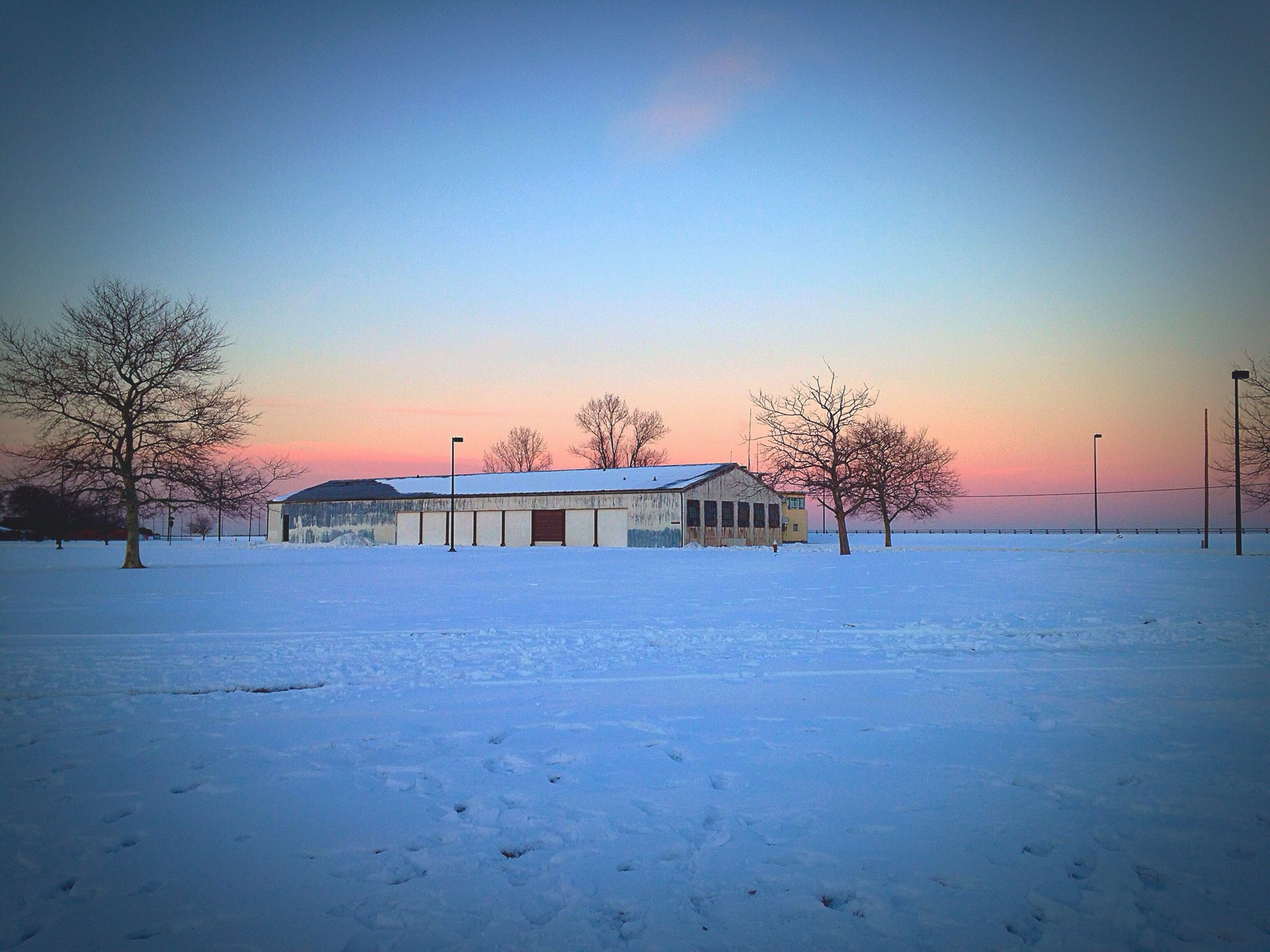 winter, snow, sunset, cold temperature, clear sky, tree, season, copy space, landscape, built structure, house, tranquil scene, tranquility, architecture, field, nature, orange color, weather, bare tree, covering