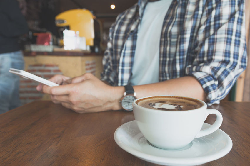 Male using a smart phone with coffee cup on wooden table. One Person Table Coffee Cup Drink Holding Coffee Cup Coffee - Drink Refreshment Lifestyles Cafe Mug Food And Drink Leisure Activity Indoors  Midsection Adult Real People Human Hand Men Crockery Wireless Technology Saucer Hand Coffee Shop