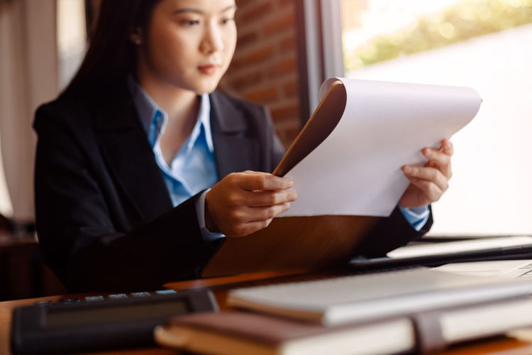 Businesswoman reading document sitting in office