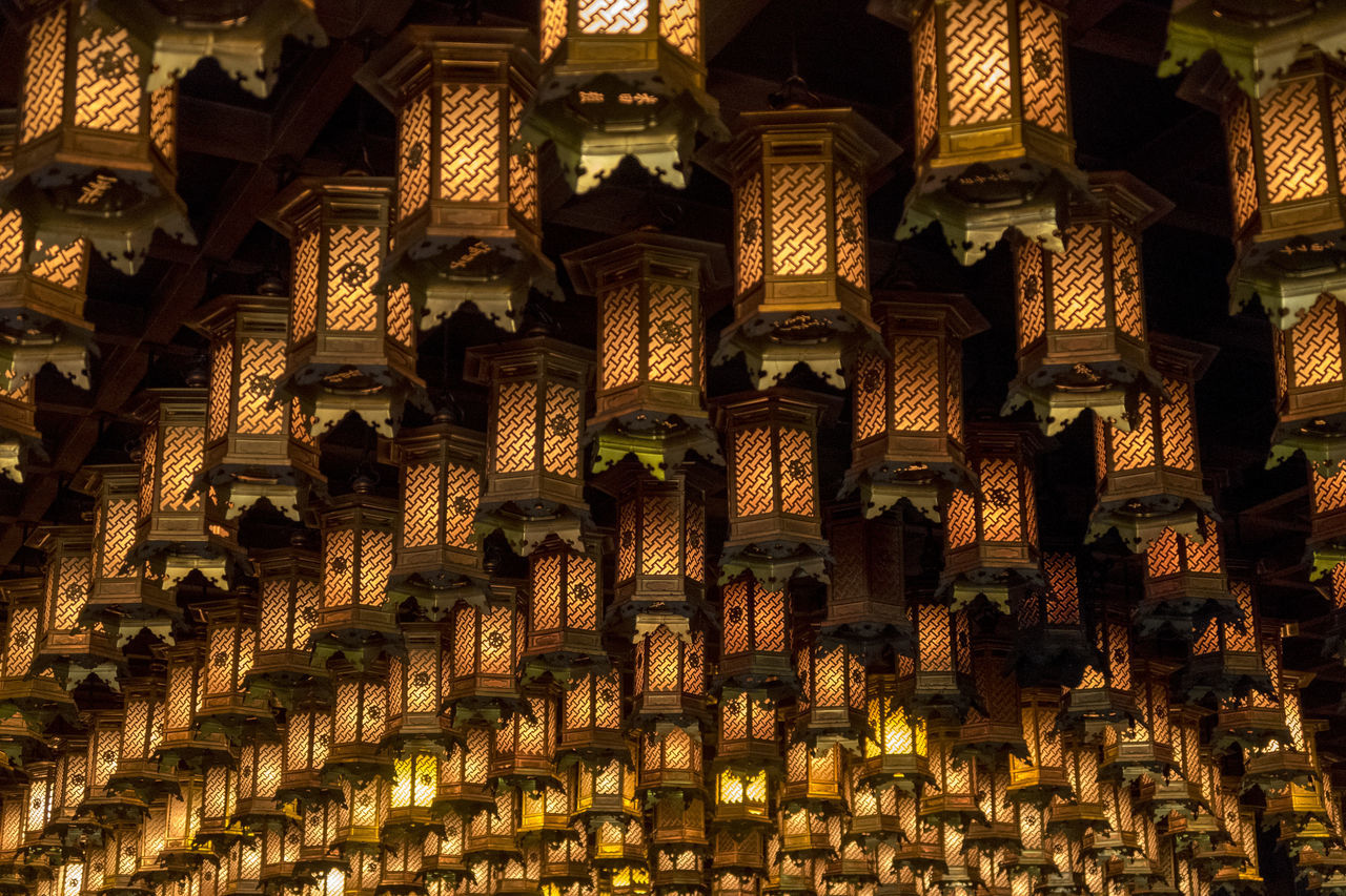 no people, in a row, large group of objects, abundance, low angle view, indoors, built structure, repetition, backgrounds, pattern, full frame, architecture, arrangement, building, illuminated, belief, religion, lighting equipment, place of worship, spirituality, order