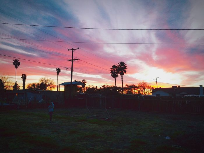 Sunset And Clouds  Colors Of A Rainbow Urban Landscape Dramatic Sky Sunset Outdoors Seasonal Fence Field Recreational Activity United States California Central Valley Area Backyard Evening Sky Backgrounds Young Girl Playing Girl In Backyard Play Fall/winter Skies Tree Colorful Sky Nature Trees And Sky Sunlight Goodbye Sunshine