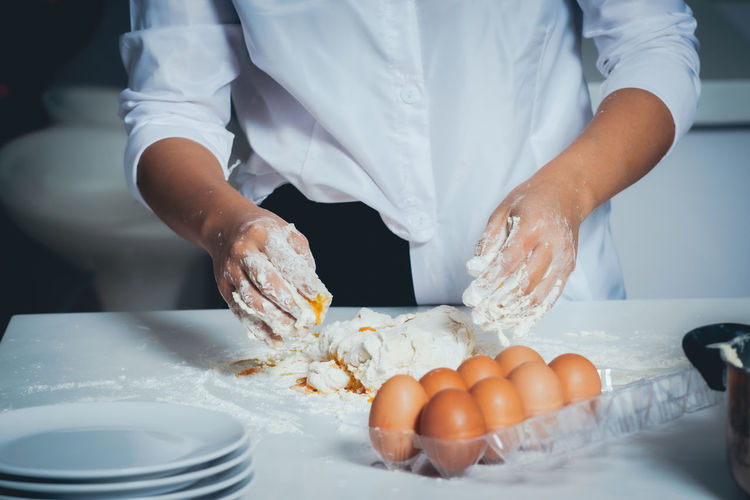 Midsection of man kneading dough in commercial kitchen