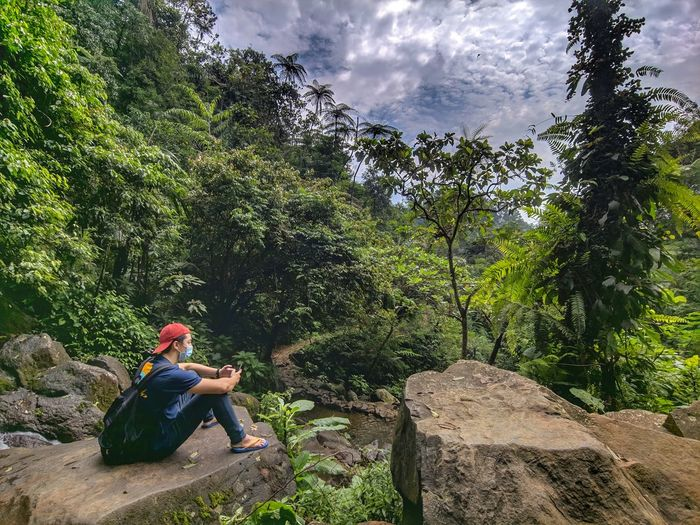 Man sitting on rock against trees and mountains