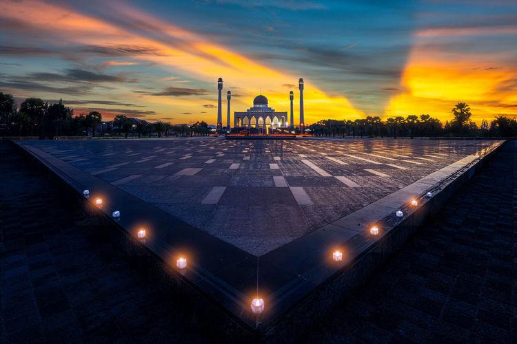 Illuminated mosque against sky at sunset