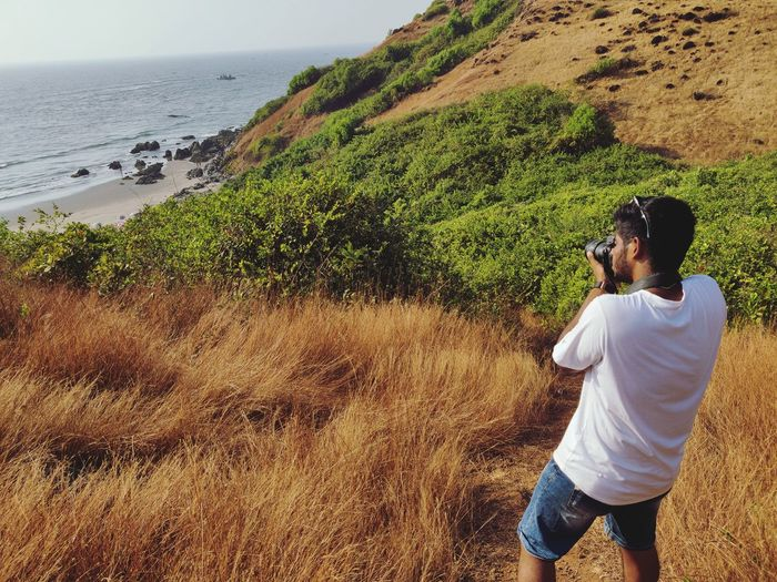 Rear view of man photographing sea