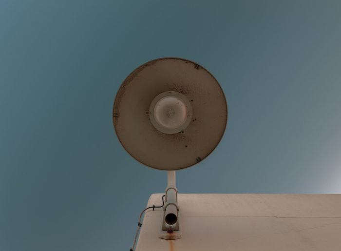 Low angle view of electric lamp against clear blue sky