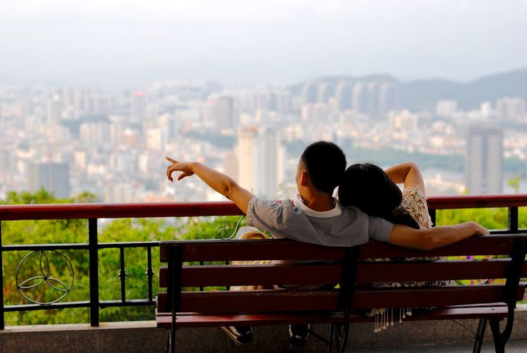 Rear view of couple sitting on balcony