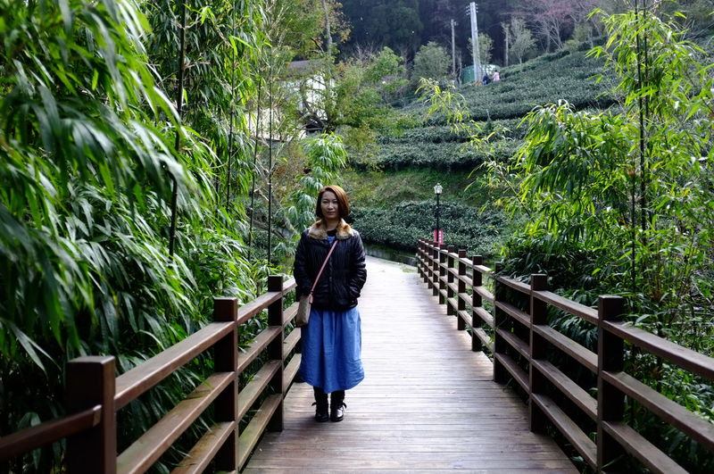 Full length portrait of woman standing on walkway at park
