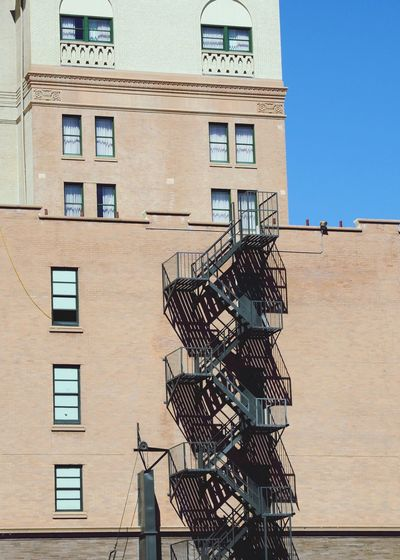 Low angle view of metallic fire escape on residential building