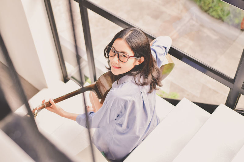 Adult Beautiful Woman Beauty Casual Clothing Eyeglasses  Front View Glasses Hairstyle High Angle View Indoors  Leisure Activity Lifestyles One Person Portrait Railing Real People Women Young Adult Young Women