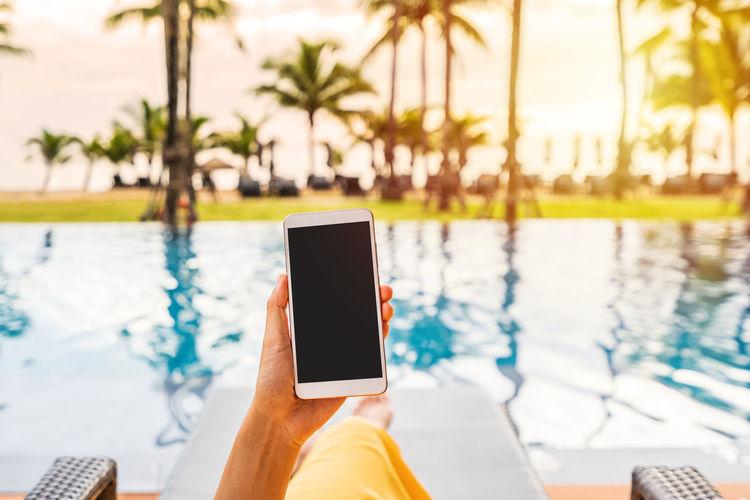 Man using mobile phone in swimming pool