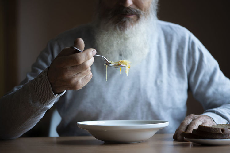 Midsection of man eating food on table