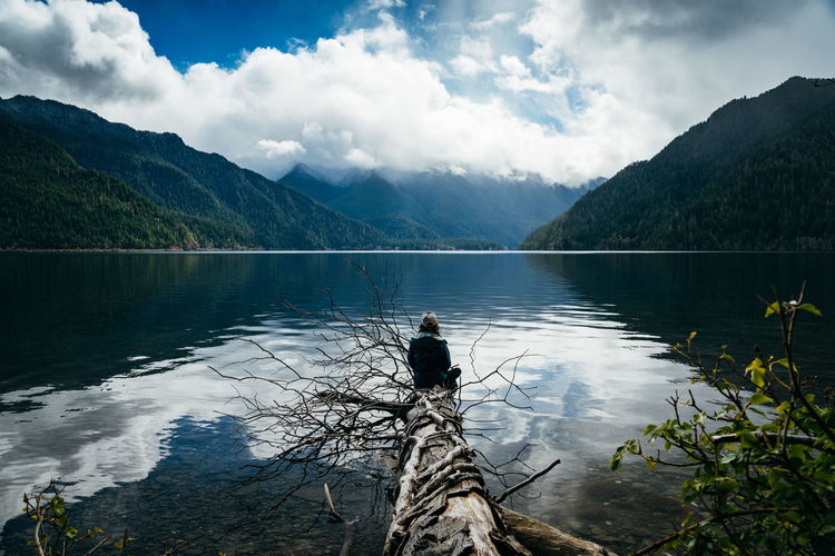 Woman sitting on broken tree while looking at lake and mountains against sky